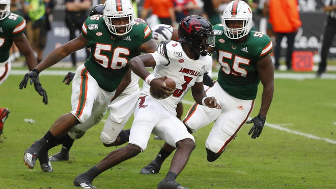 Miami linebackers Shaquille Quarterman (55) and Michael Pinckney (56) rush Louisville quarterback Micale Cunningham in November.
