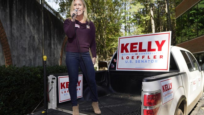 Republican candidate for Georgia's 14th congressional seat Marjorie Taylor Greene speaks from the bed of a pickup truck during a campaign rally Saturday, Oct. 31, 2020, in Roswell, Ga.