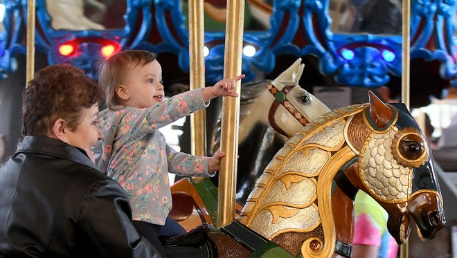 A youngster rides an armored horse at the Richland Carrousel Park in Mansfield.