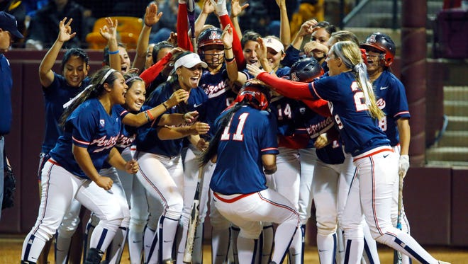 Arizona teammates wait to swarm Mo Mercado (11)  after her two-run home run in the top of the 8th inning during their NCAA softball game  against Arizona State Sunday March 30, 2014 in Tempe, Ariz.