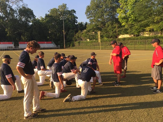 Licking County 16u Athletics' head coach Mark Hogue consoles his team, after their 15-game winning streak, and season, came to an end Saturday at St. Charles High School.