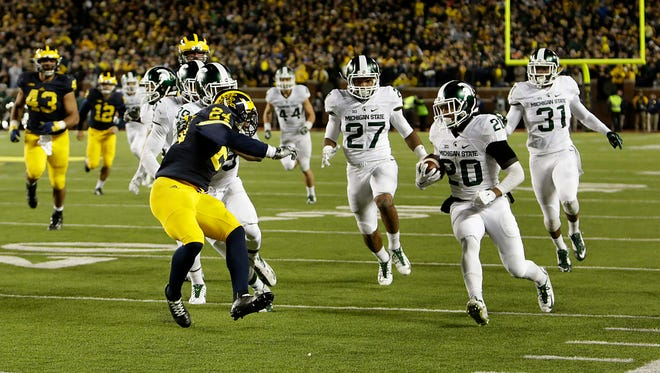 Jalen Watts-Jackson (20) runs down the sideline with the football for the winning touchdown, after he picked up a fumbled punt on the final play of the game between Michigan and Michigan State in Ann Arbor, Oct. 17, 2015. Watts-Jackson's score gave MSU an improbable 27-23 win.