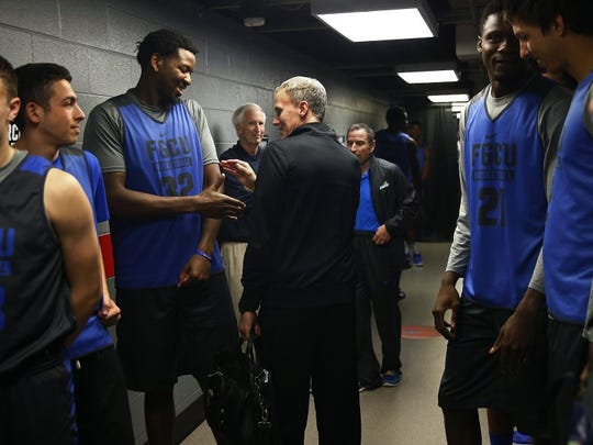 Former Florida Gulf Coast head coach and current Southern California head coach Andy Enfield, center, says hello to Florida Gulf Coast forward Antravious Simmons (32) Wednesday, March 16, 2016 at PNC Arena in Raleigh, N.C. The Florida Gulf Coast men's basketball team practiced and met with media for Thursday's opening round of the NCAA Tournament matchup with North Carolina. (Corey Perrine/Staff)