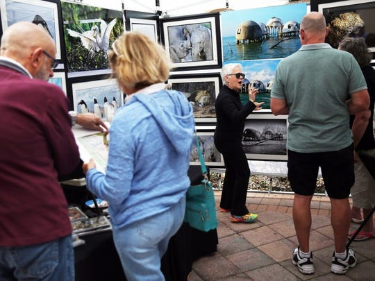 Barbara Parisi of Marco Island, center, talks to visitors about her husband Joe's photographs during the Left Bank Art Fest at the Esplanade Shoppes on Marco Island on Sunday, Feb. 28, 2016. (Dorothy Edwards/Staff)
