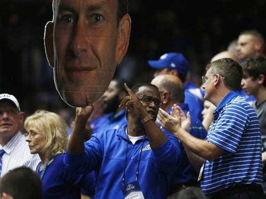 Florida Gulf Coast President Wilson G. Bradshaw points to a photo of Florida Gulf Coast head coach Joe Dooley during the second half Tuesday, March 15, 2016 at the University of Dayton Arena in Dayton, Ohio. Florida Gulf Coast faced Fairleigh Dickinson in the First Four, a play-in game to the NCAA Men's Basketball Tournament. FGCU won 96-63. (Corey Perrine/Staff)