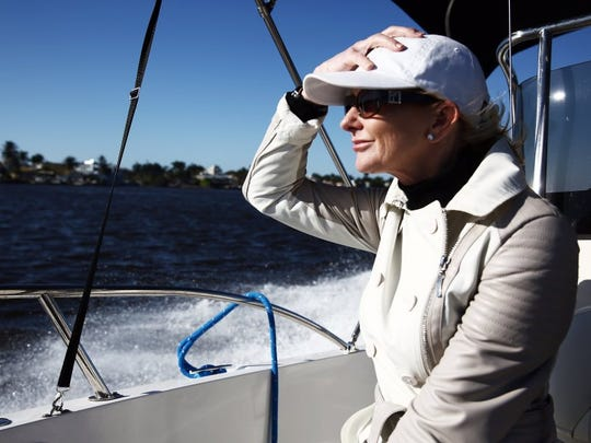 Naples Mayoral Candidate Teresa Heitmann holds on to her hat as she rides in her boat with her family on Sunday, Feb. 7, 2016. (Dorothy Edwards/Staff)