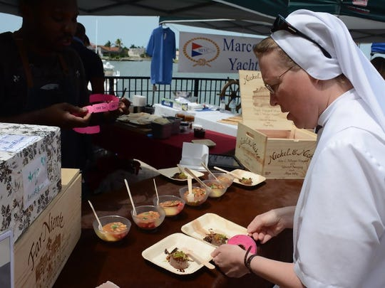File, 2016: Sister Suzanne Dauwalter, one of the event judges, tries the tenderloin at the Ario booth. The 26th annual Taste of Marco brought a crowd to the Esplanade shopping center.