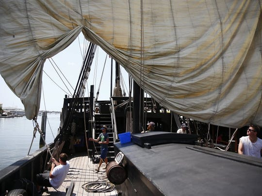 Crew members unfurl a sail on the Pinta Tuesday, April 12, 2016 at Tin City in Naples.