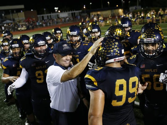 Naples' Head Coach Bill Kramer congratulates Naples' Crandall Maines (99) after defeating Lely Friday, Oct. 9, 2015 at Naples High School's Staver Field in Naples, Fla. The Golden Eagles faced The Trojans in the 42nd Annual Coconut Bowl. Naples won 69-0. (Corey Perrine/Staff)