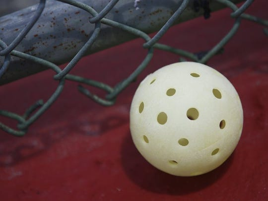 A stray pickleball ball is shown at the fence line