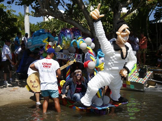 Ryan Price, center, boards the Balloon Buccaneers canoe complete with an Elvis ballon statue and guitar oars Saturday, May 14, 2016 at Crayton Cove in Naples, Fla. The 40th, and presumably final Great Dock Canoe Race, concluded with a disco theme   ' because it started in 1977   'titled 'The Last Dance.' Hundreds showed up and dozens competed in themed, amateur, VIP and pro categories. Kim Kelsey and Anita Allen won the pro event with a time of 20:48 and 18:48 adjusted for a two minute handicap, since they were a mixed sex team. Best overall time was from father son tandem Peter Jenks, 60, and Casey Jenks, 31. (Corey Perrine/Staff)