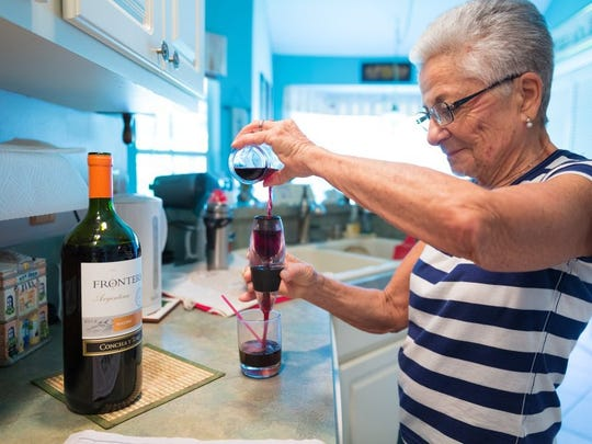 Naples resident Gloria Jackson, 84, pours herself four ounces of red wine as part of a lunchtime ritual on Tuesday, May 17, 2016, in her East Naples home. (David Albers/Staff)