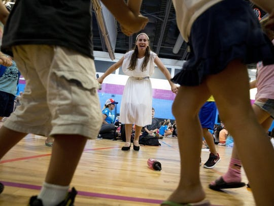 Maya Ariad, 17, a member of the Israel Scouts, dances with children during a group song as part of the Israeli Friendship Caravan performance at the Naples YMCA on Thursday. The caravan, made up of 10 Israeli teenagers, travels throughout the United States as ambassadors for Israel, spreading goodwill and friendship. (Luke Franke/Staff)