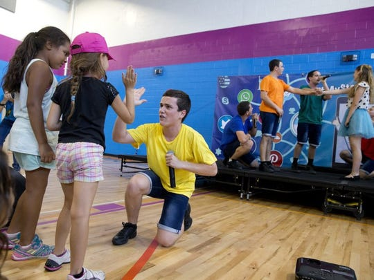Yuval Moran, 17, a member of the Israel Scouts, jumps off stage to high-five children in the crowd during the Israeli Friendship Caravan performance at the Naples YMCA on Thursday. The caravan, made up of 10 Israeli teenagers, travels throughout the United States as ambassadors for Israel, spreading goodwill and friendship. (Luke Franke/Staff)