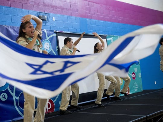 As an Israeli flag flies just off stage as members of the Israel Scouts Friendship Caravan perform during their final song at the Naples YMCA on Thursday. The caravan, made up of 10 Israeli teenagers, travels throughout the United States as ambassadors for Israel, spreading goodwill and friendship. (Luke Franke/Staff)