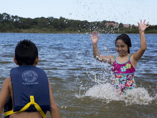 Jessica Garcia, 8, plays with her cousin Aries Ayala, 6, both of Naples, in Lake Avalon at Sugden Regional Park on June 23, 2016 in Naples, Florida. (Nicole Raucheisen/Staff)