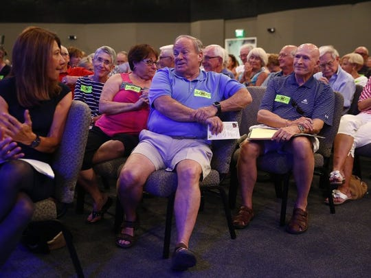 In this file photo, patrons voice concern over potential construction as Neale Montgomery, a land use attorney with Pavese Law Firm, left, listens June 27, 2016, at Living Waters Church in Estero. WCI Communities held a public information meeting to provide a general overview of Pelican Landing's proposed development of four 22-story high rise towers in the Raptor Bay Golf Club.