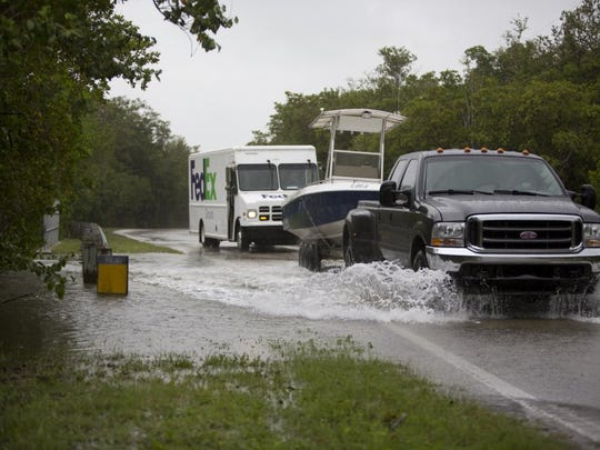 Vehicles drive through flooding on Goodland Road in Goodland on June 6, 2016. The flooding is being caused by heavy rain as a result of Tropical Storm Colin.