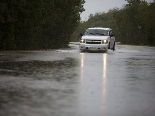 An SUV drives through flooding on Goodland Road in Goodland on June 6, 2016. The flooding is being caused by heavy rain as a result of Tropical Storm Colin.