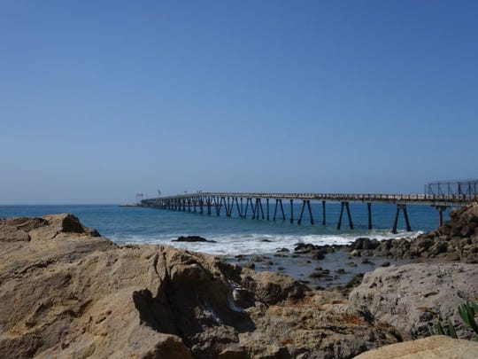 A gated wooden bridge separates Rincon Island from the shore at Mussel Shoals.
