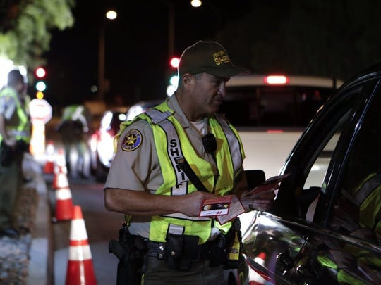 Ventura County Sheriff's Deputy David Anaya hands out pamphlets during a DUI and driver's license checkpoint in Moorpark in May 2016.