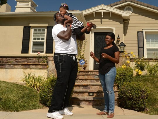 KAREN QUINCY LOBERG/THE STAR Jamon Brown, a guard for the Los Angeles Rams, his daughter Micayla, 3, and wife Micquel Brown recently moved into this Dos Vientos house in Newbury Park.