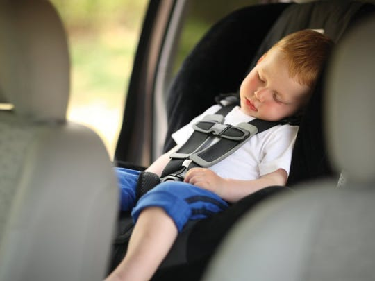 Boy sleeping in child car seat.