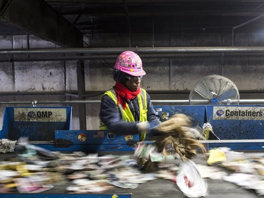 Bridgett Boyd sorts through paper at the ReCommunity recycling plant at 3197 Farrisview.