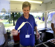 Geoff Calkins, in pursuit of an offbeat column during the 2016 FedEx St. Jude Classic, works a shift in a Pronto Pup stand.