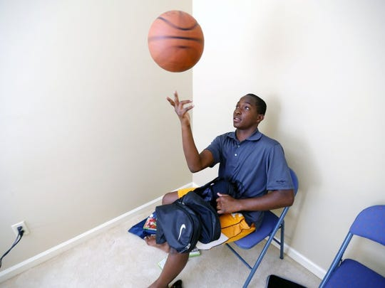 Chauncy Black sits in the corner of his new bedroom playing with a basketball on Aug. 1, 2016. Black and his family moved into a new home, which was the result of a public outpouring of donations that totaled more than $340,000.