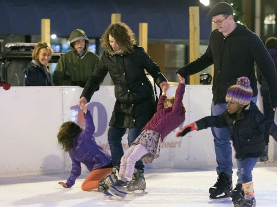 A family ice skates together at the Holidays on Ice skate rink in Market Square on New Year's Eve, Dec. 31, 2015.
