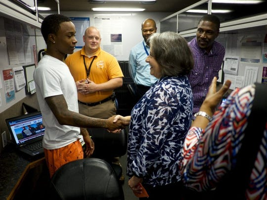 Knoxville Mayor Madeline Rogero greets job seeker John Mack in the Career Coach Bus on Friday, August 12, 2016, at Lonsdale Homes. In the background are Career Specialist Scott Wallace, left, Career Specialist Alonzo Lewis, and job seeker Ron Crenshaw. The career fair at Lonsdale Homes is supported by Knoxville's Community Development Corporation (KCDC), Save Our Sons, the Tennessee Department of Labor and Workforce Development, Job Corps, Workforce Connections and the City of Knoxville in response to the 'Stop the Violence' community forum held earlier this year at Fulton High School following the death of Zaevion Dobson.
