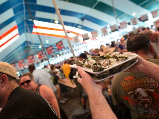 COURTNEY SACCO/CALLER-TIMES A man carries two trays of oysters through a crowd of people Saturday, March 5, 2016, during the 37th annual Fulton Oysterfest in Fulton.