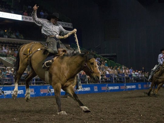 COURTNEY SACCO/CALLER-TIMES A saddle bronc rider competes in the opening night of Rodeo Corpus Christi at the American Bank Center, Thursday, April 14, 2016.
