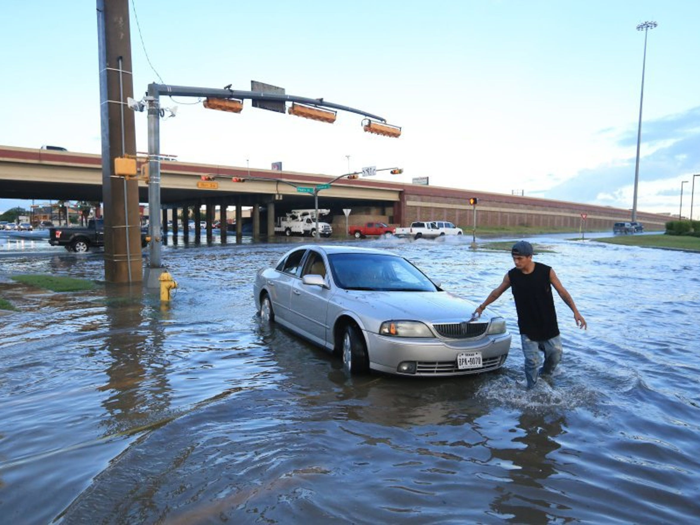 Rachel Denny Clow/Caller-Times  In this 2016 file photo, Steven Galindo walks stands alongside his car as floodwaters inundate Kostoryz Road. Federal flood maps predict damages based on rainfall totals, but don't account for storm water system capacity, officials say.