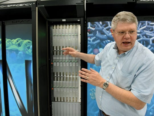 Project director Buddy Bland shows the Titan supercomputer April 20, 2016, at Oak Ridge National Laboratory. Titan was later replaced by the Summit supercomputer.