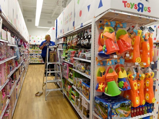 Angela Herron stocks shelves at the new Toys 'R' Us outlet store in the Tanger Outlets in Sevierville Thursday, April 28, 2016.