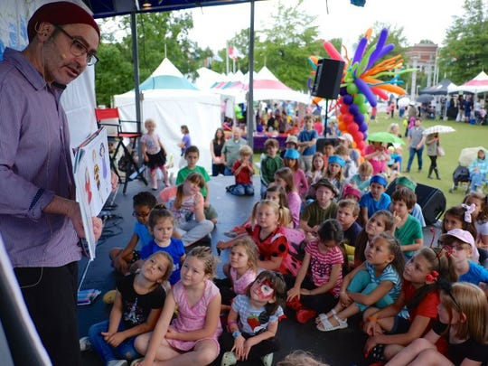 David Soman reads the children's book 'Ladybug Girl' to a group of children on the main stage during the Children's Festival of Reading at World's Fair Park on Saturday, May 21, 2016. (Shawn Millsaps/Special to News Sentinel)