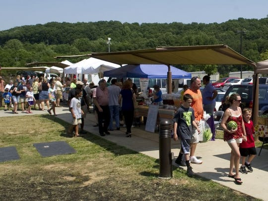 Vendors and customers line the sidewalk at New Harvest Farmers' Market.