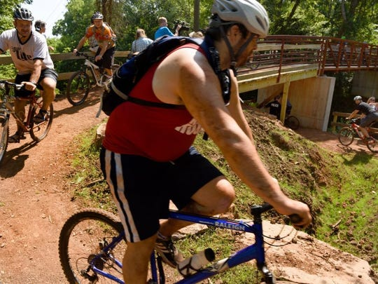 Appalachian Mountain Bike Club riders are the first to cross the new Red Bud bridge after an opening ceremony in South Knoxville in this September 2016 file photo. The 50-foot bridge connects the Urban Wilderness to the Baker Creek Preserve, a 100-acre mountain bike park and adventure playground across from South-Doyle Middle School. It was funded entirely by private dollars from the Legacy Parks Foundation and the Appalachian Mountain Bike Club.