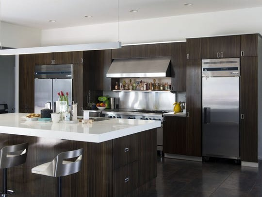 AFTER: Following the renovation, the kitchen features stainless steel and solid white quartz countertops, commercial grade appliances, and zebra wood cabinets.