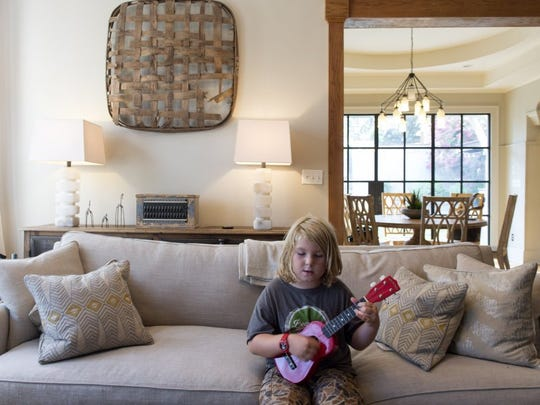 Oliver strums his guitar on the sofa in the living room. The dining area and doors to the rear garden are visible through the large doorway. (SAUL YOUNG/NEWS SENTINEL)