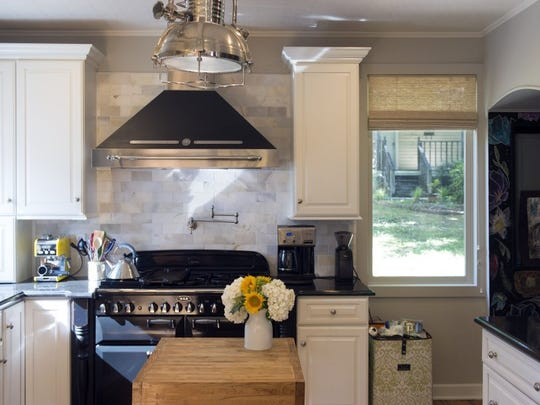 The Aga range came with the house. Scott and Lisa painted the cabinets white and added the hood and industrial-style light fixture. The butcher block island came from Sherrill Perkins, the last farmer at the old farmers market on Market Square. (SAUL YOUNG/NEWS SENTINEL)