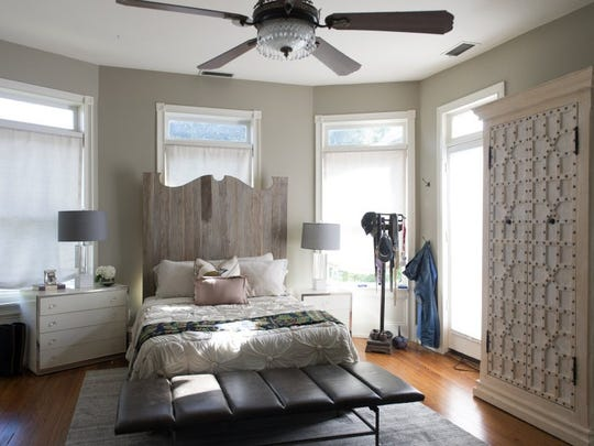 The master bedroom features a bed with a reclaimed wood headboard and an eclectic mix of furniture in neutral tones.