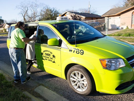 COURTNEY SACCO/CALLER-TIMES Green N Go cabdriver Phillip Benesh opens the door and helps a fare into the back of his cab Feb. 4, 2016. Several discussions on taxis and transportation network companies are scheduled before the City Council takes a vote on an ordinance for companies like Uber. A vote could come before the council as early as May.