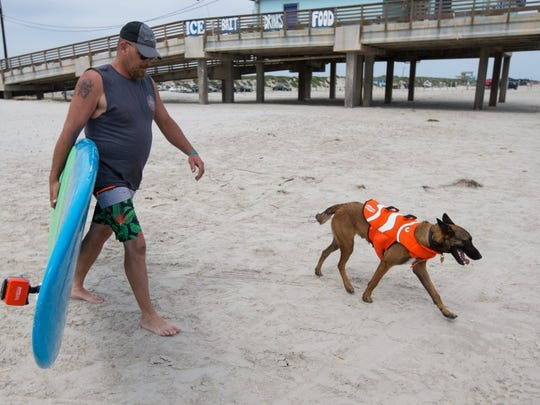 COURTNEY SACCO/CALLER-TIMES Jason Hibbeler and his dog Halo walk down the beach Friday, April 8, 2016, at Horace Caldwell Pier in Port Aransas.