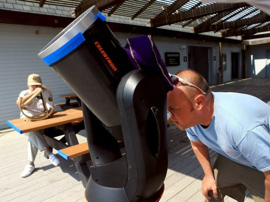 Dennis Staples looks through a telescope as the planet Mercury passes in front of the sun during the Mercury Transit on Monday at the Padre Island National Seashore.