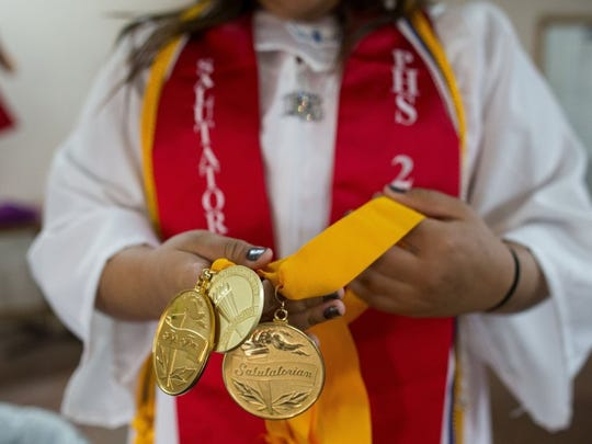 COURTNEY SACCO/CALLER-TIMES Premont 2016 salutatorian Rebeca Nevarez puts on her medals during at the Oasis Restaurant before heading to the senior walk at the elementary school, Tuesday, May 31, 2016.