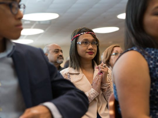 COURTNEY SACCO/CALLER-TIMES Juliet Hinokose, who immigrated from the Philippines, wears a red, white and blue headband during a citizenship ceremony in 2016 at the U.S. District Court for the Southern District of Texas.