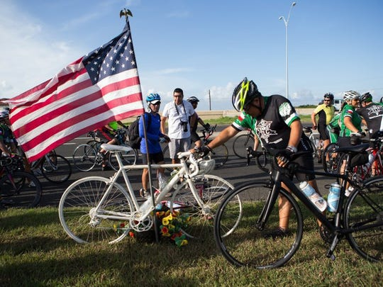 COURTNEY SACCO/CALLER-TIMES A cyclist stops at the ghost bike left in honor of Andy Heines, who died early this week from injuries he sustained in a hit-and-run crash.